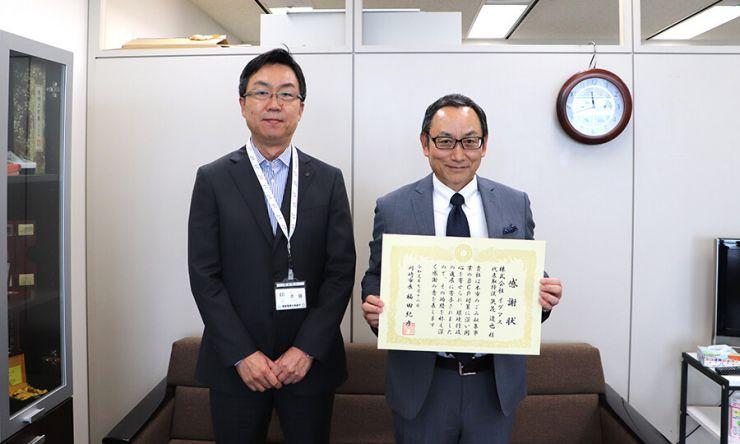 川崎市 環境局長様(左)/ 弊社 代表 矢花達也 (右)